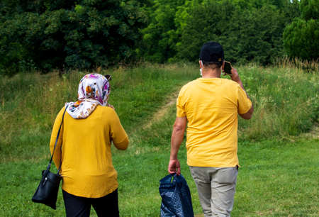 Arabs dressed in yellow at the park with phone and bags