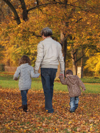 small children with grandfather playing in the park in autumn photo