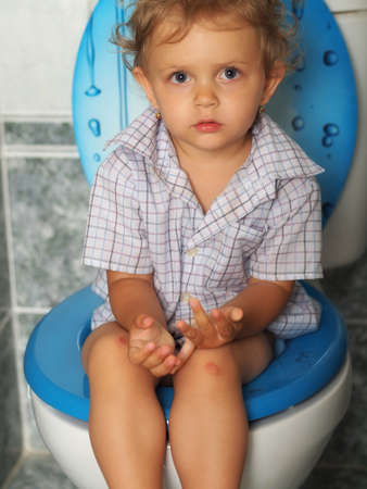 pee pee: little baby sitting on the toiltet Stock Photo