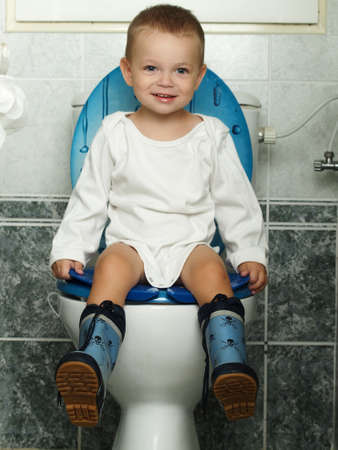 toilet bowl: little baby sitting on the toiltet Stock Photo