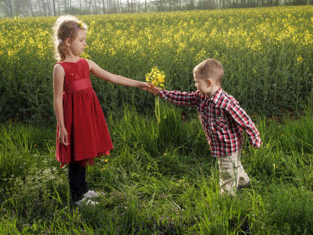 Little girl and boy with bouquet of dandelions photo