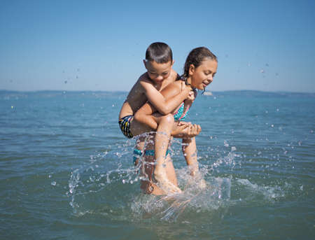 Little girl and littel boy playing in water