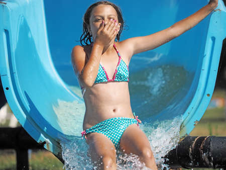 Little girl playing in a water park Banco de Imagens