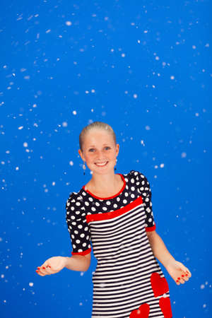 Young Girl in Dress Smiling and Catching Snow Hand on Blue Background