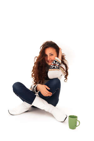 Young Girl with Curly Hair in a Sweater and White Boots Sits on a White Isolated Background with a Cup of Tea