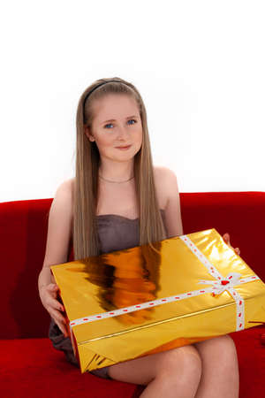 Young Healthy Woman with Long Hair and Blue Eyes Sits on the Sofa with a Big Gift Stock Photo