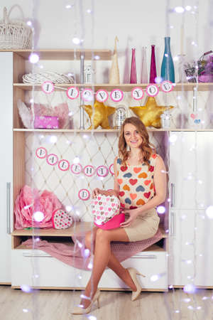 Young beautiful woman with a gift and garlands sits on the Interior Valentine's Day. High quality photo