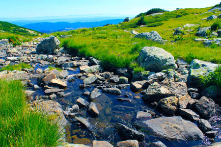 High mountain river running amongst big rocks in a sunny spring day Stock Photo