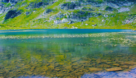 Closeup of a high mountain lake in a sunny spring day Stock Photo