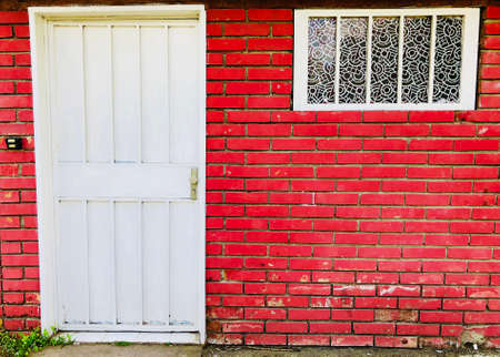 Countryside brick house outide facade frony door with bell and window Stock Photo