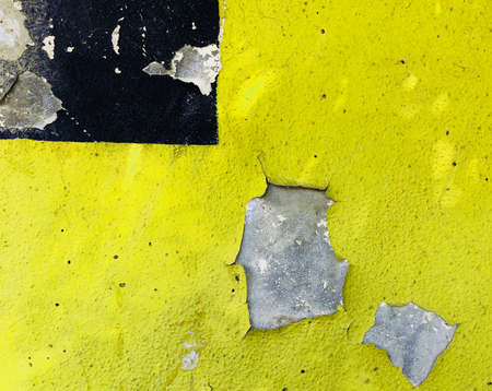 Old vintage wall with cracked yellow and black paint showing stones behind vibrant color background