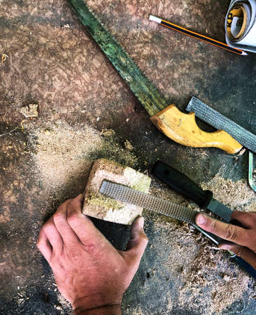 man working on a piece of wood rasping outdoors labor craft concept top view
