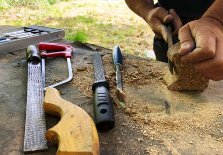 man working on a piece of wood rasping outdoors labor craft concept Stock Photo