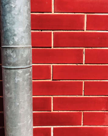 red brick house wall outdoor background with a metal stovepipe