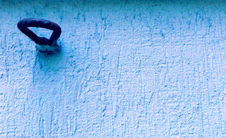 dark rusty metal ring biult in a light blue rough vintage grungy wall in illustration of a hooking concept Stock Photo