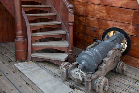 Antique bronze cannon on board and old wooden ship aimed through a port hole in the side hull alongside a flight of steps