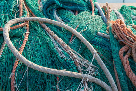 Pile of assorted green fishing nets and old weathered ropes in a closeup full frame background view