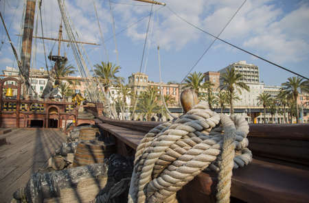 Ropes tied to a stanchion on the wooden galleon Neptune with a view over the deck of the port of Genoa, Italy