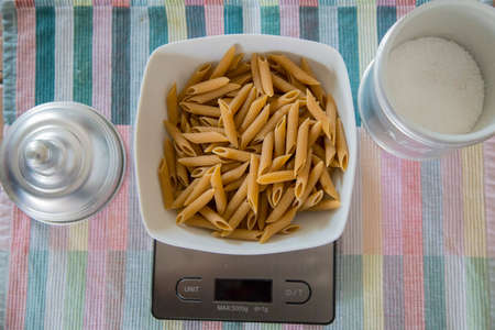 horizontal image with top view of a plate of wholemeal pasta on a digital scale 写真素材