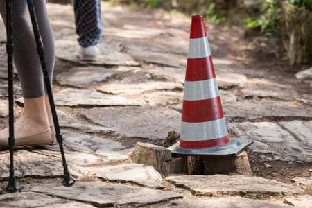 horizontal conceptual image of a red and white plastic cone for signage, in a place with broken road Stock Photo
