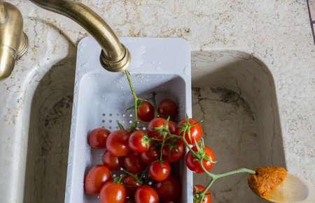 image of cherry tomatoes in plastic container and wooden spoon with tomato sauce 写真素材