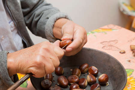 horizontal image with detail of two hands preparing chestnuts, inside a pan 免版税图像