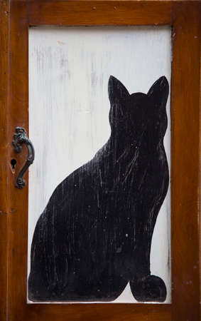 vertical image of a small door with drawn a black cat