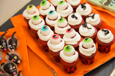 horizontal image with detail of a tray of desserts with cream and strawberry decorated with fake eyes for the halloween party