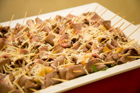 horizontal image with close detail of roast beef nuggets and cheese shavings a typical Italian appetizer