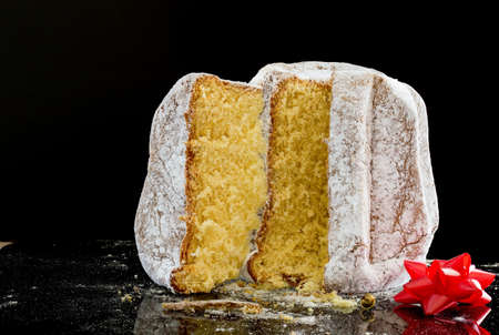 horizontal image with close up detail of a typical Italian Christmas cake, the pandoro cut into slices with a black background Banco de Imagens
