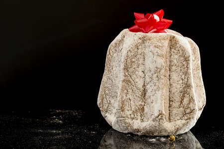 horizontal image with close detail of a typical italian Christmas cake, the pandoro with a black background Banco de Imagens