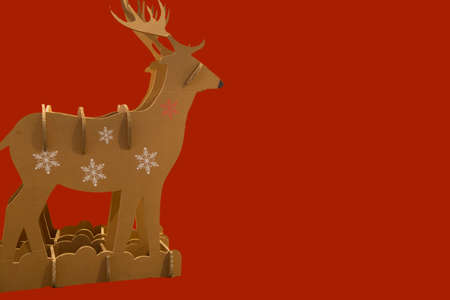 horizontal image of a cardboard construction representing a reindeer used as a Christmas decoration with a red background