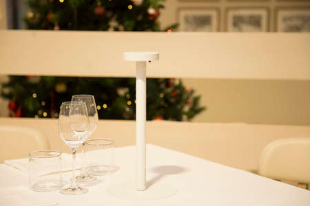 horizontal image with detail of a white table with above three empty glasses with a christmas tree in the background