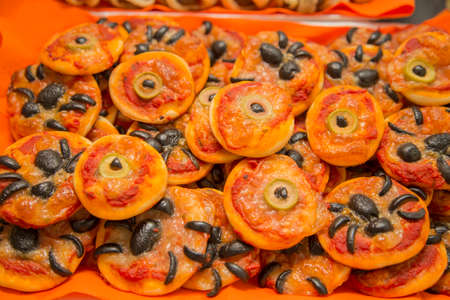 horizontal image with detail of a tray of pizzas decorated for halloween party
