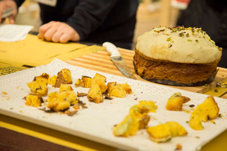 horizontal image with detail of a panettone filled with pistachio cream cut to be tasted by the public, photographed at a food fair in Italy Banco de Imagens