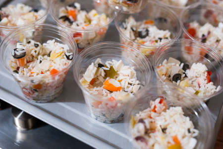 horizontal image with detail of various appetizers served in transparent plastic cups