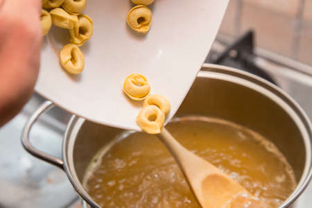 horizontal image with detail of a plate with italian tortellini pasta while cooking in a hot broth