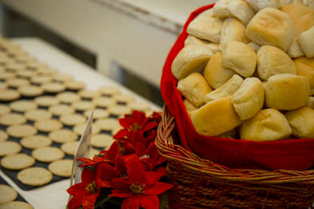 horizontal image with close detail of a red wicker basket with bread inside, photographed during a party