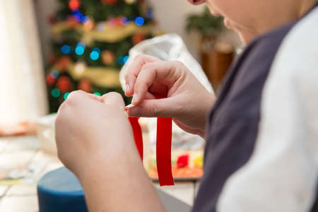 horizontal image with detail of a womans hand preparing a christmas gift with a red ribbon