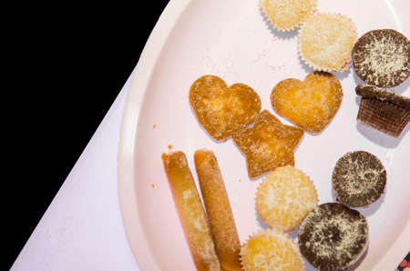 horizontal image with detail and top view of a plate with biscuits of various shapes and flavors Banco de Imagens