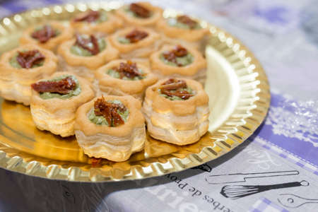 horizontal image with vol-au-vent detail with pesto sauce and dried tomatoes, served on a tray and prepared for a party