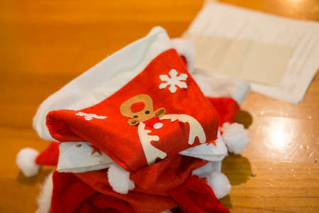 horizontal image with detail of some red Santa Claus hats used for a school performance, set on the stage