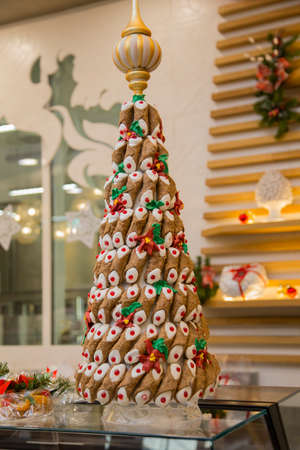 horizontal image with detail of a Christmas tree made with cannoli stuffed with an Italian pastry