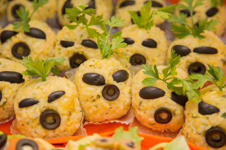horizontal image with detail of rice balls with black olives decorated for halloween party