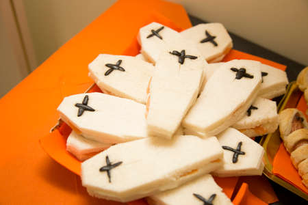 horizontal image with detail of coffin-shaped sandwiches prepared for halloween party