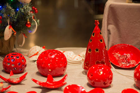 horizontal image with detail of red ceramic Christmas objects of various shapes