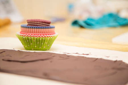 horizontal image with detail of a strip of chocolate on a table for the preparation of muffins
