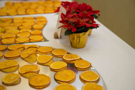 horizontal image with detail of thin slices of orange arranged neatly on a tray prepared for a party