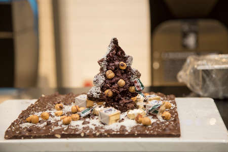 horizontal image with detail of a Christmas tree made entirely of chocolate with hazelnuts in a pastry shop Banco de Imagens