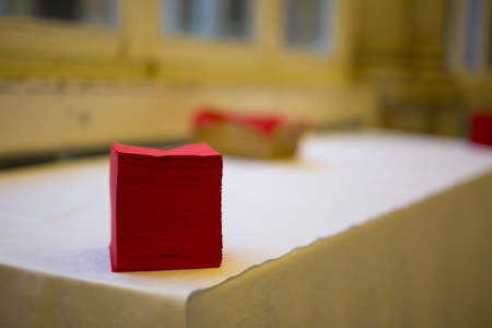 horizontal image with detail of a stack of red napkins on a table while preparing a buffet Banco de Imagens
